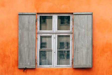 Old wooden window shutters of an european house with orange painted facade