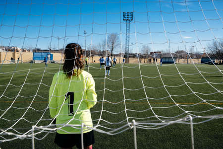 Female goalkeeper standing on goal on the soccer field Standard-Bild