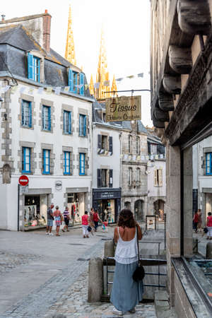 Woman standing on street amidst old buildings in the centre of Quimper Editorial