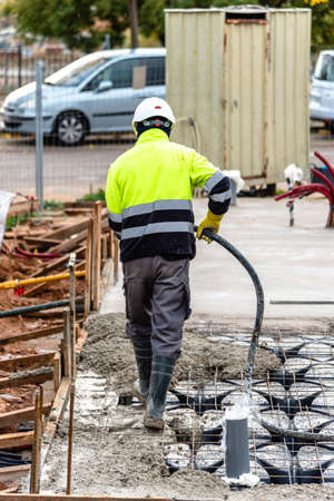 Construction worker is pouring concrete in slab