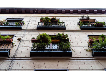 Low angle view of old cast iron balconies of old residential building in Lavapies quarter in Madrid Standard-Bild