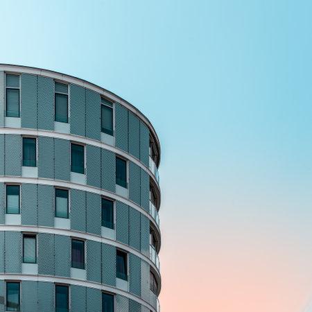 Minimalist apartment building in Hamburg against beautiful orange and teal blue sky Redactioneel