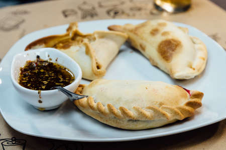 Argentinean pie with spicy sauce on white plate Stockfoto