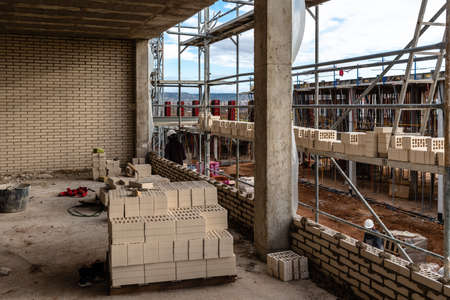Bricks on scaffolding ready to be placed in facade Stockfoto