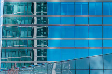 Office building and reflections against blue sky
