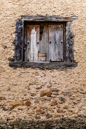 Wooden window on old adobe wall, Spain