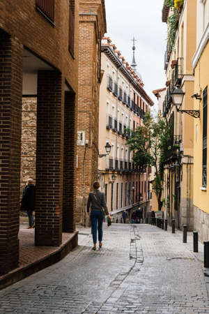 Street scene with unidentified people walking by a narrow street in historic centre of Madrid Editorial