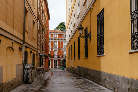 mpty narrow street with closed sidewalk cafe during pandemic in Madrid