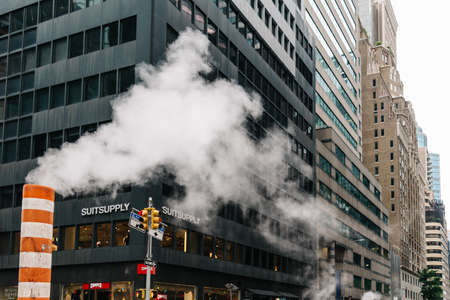 Low angle view of steam coming out stack for venting the district heating system in New York Editorial