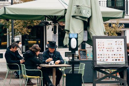 Unidentified People Sitting in a Sidewalk Cafe Terrace in Madrid