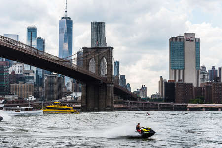Cityscape of Downtown of Manhattan and Brooklyn Bridge with jet ski Editorial