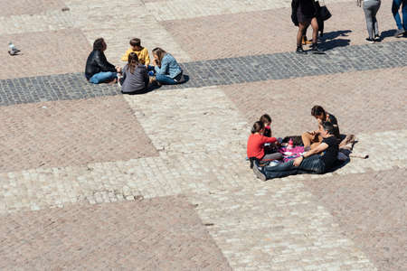 People eating sitting on the floor in Plaza Mayor Square in Madrid