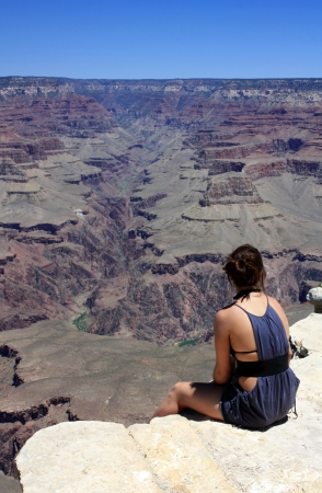 girl sitting on the edge of the grand canyon photo