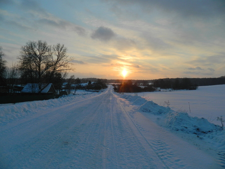 Winter road, going to the distance, against a background of a bright sunset, during a small snowfall. Great illustration