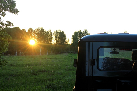 The car is cross-country, against the background of summer nature, during the evening sunset.
