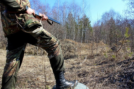 A novice hunter with a firearm on a spring hunting game.