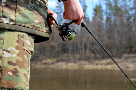 Angler in camouflage clothing, fishing on spinning Stockfoto