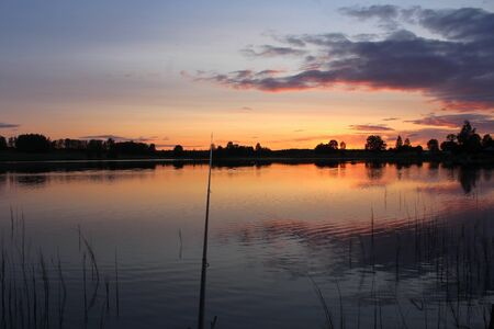 Fishing on the lake on a warm evening, in the middle of summer. A unique image of the surrounding nature.