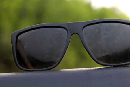 Sunglasses on the roof of a car during sunrise against the backdrop of the surrounding nature Standard-Bild