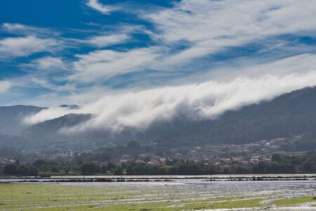 A sea of white clouds going down the mountains to the village of Noia in Galicia, Spain and reaching the sea ( low tide).