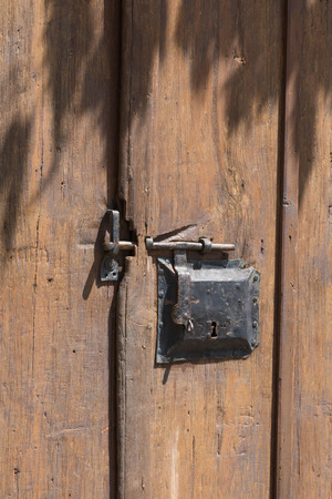 ancient blacksmith: Medieval door lock, old wooden door with iron lock.