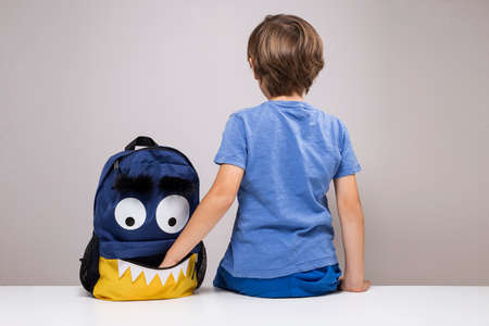 Young boy with his hand inside pocket of his school bag, open funny monster face backpack, back to school concept