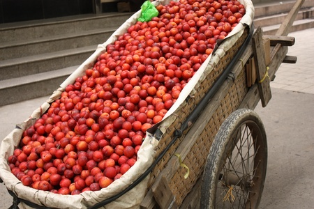 haggling: Hand cart full of plums Stock Photo