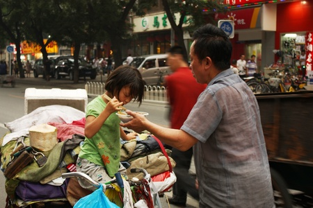 Homeless family in a street of Beijing, China - July 16, 2010 Stock Photo - 8965179