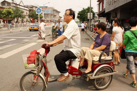 motorized bicycle: Motorbike driver and passenger in Beijing, China - July 17, 2010