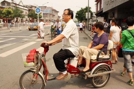 Motorbike driver and passenger in Beijing, China - July 17, 2010