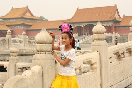 head wear: Chinese girl in traditional head wear is standing on the bridge across Golden Water Canal in Forbidden City in Beijing, China - July 17, 2010