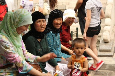 Chinese Muslim family with traditional headdress in Forbidden city, Beijing - July 17, 2010
