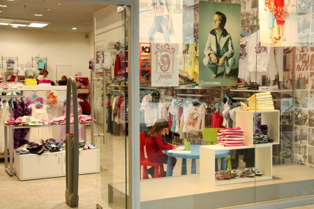 Children clothes shop window and a small customer in it , Moscow, Russia - April 10, 2011