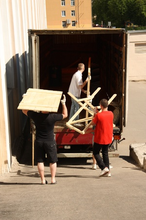 Removal men working with pieces of furniture photo