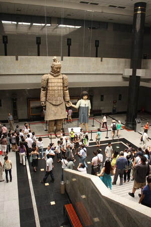 Big terracotta warrior Statue with a puppet girl in the Terracotta warriors museum in Xian, China - July 24th, 2010