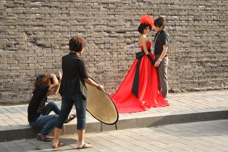 Photographer with assistant and models posing in street of China - July 24th, 2010