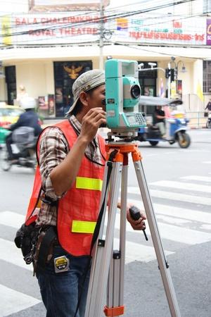 surveyor: Mujer geodesta hacer levantamiento geodésico con Altometer, Bangkok, Tailandia - 07222011