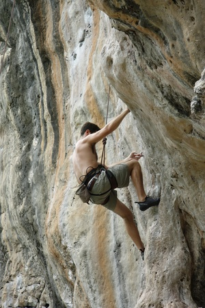 Rock climber young man with safety equipment photo