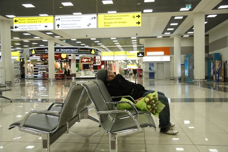 delay: Young man waiting at the airport for his beloved, Sheremetievo Internaitonal Airport, Moscow, Russia 04.11.2011