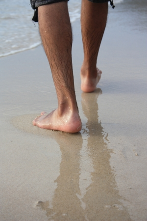 sandy feet: Legs of Man walking on beach Stock Photo