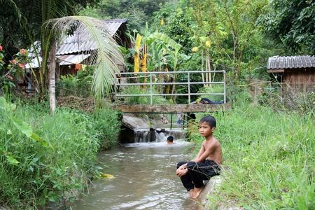 Thailand ländliche Landschaft mit einem kleinen Jungen sitzen am Ufer des Flusses, Pai, Thailand - 2011.01.08