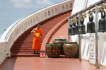 Buddhist monk and bells at the famous Bangkok landmark - The Golden Mountain, Thailand