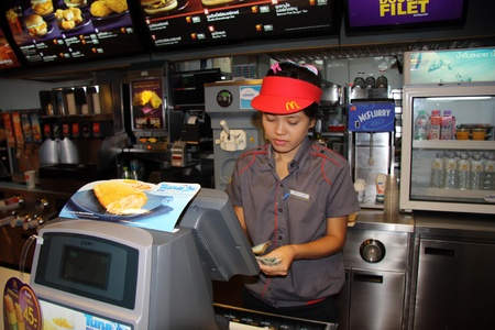 Counter of Mc Donalds cafe and young female worker in Bangkok, Thailand - 25.07.2011 Stock Photo - 12512788
