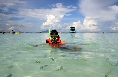Young man snorkeling at Phi Phi island in Thailand photo