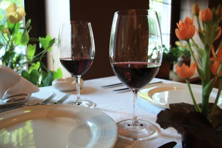 night table: Dinner for two persons with glasses of red wine Stock Photo