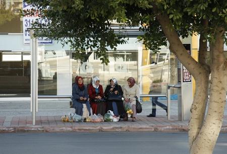 burka: Donne musulmane con i loro acquisti in attesa di un autobus, Antalya, Turchia - 29.11.2011