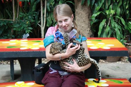 turismo ecologico: Joven mujer de raza caucásica la alimentación del bebé leopardo, Tailandia