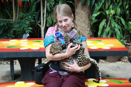 Young Caucasian girl feeding baby leopard, Thailand photo