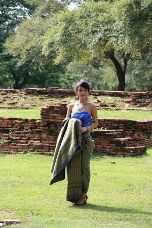 thailand silk: Beautiful girl in Thai native costume posing at ancient ruins of Ayutthaya, Thailand - 03.08.2011