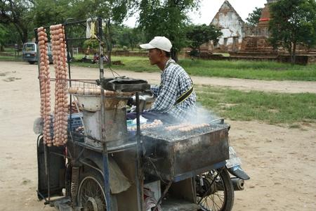 Poor Rural vendor making grilled sausage in Ayutthaya, Thailand - 03.08.2011